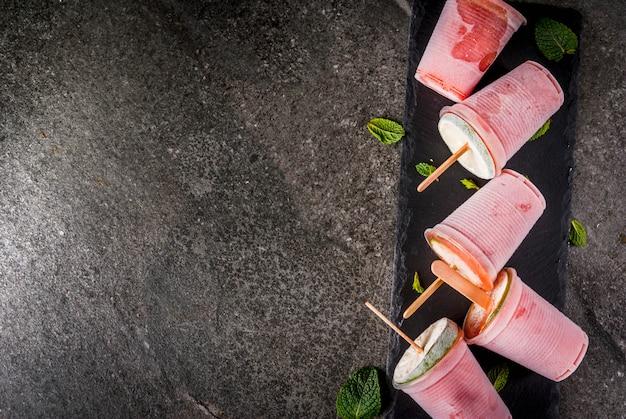 Zelfgemaakte ijsijslollys. bevroren drankjes. bevroren cocktail van watermeloen of bessen, munt en limoen.