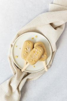 Zelfgemaakte ijslolly op een stokje met chocolade cashewnoten op een handdoek
