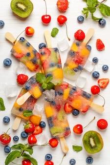 Zelfgemaakte ijslollys met bessen en fruit.