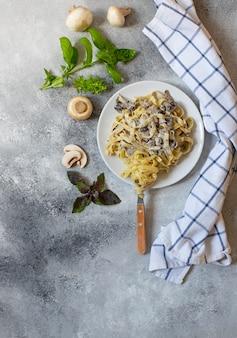 Zelfgemaakte italiaanse fettuccine pasta met champignons en roomsaus geserveerd op een witte plaat met basilicum (fettuccine al funghi porcini). traditionele italiaanse keuken. grijze achtergrond, bovenaanzicht, kopie ruimte