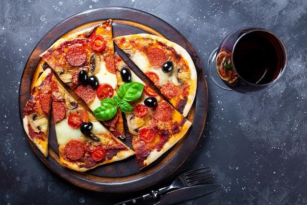 Zelfgemaakte italiaanse pizza met mozzarella, pepperoni worstjes, olijven en basilicum en een glas rode wijn op het tafelblad.