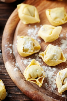 Zelfgemaakte italiaanse traditionele tortellini op de houten tafel