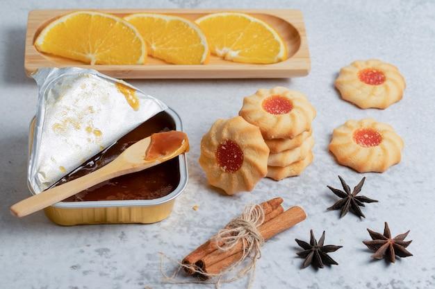 Zelfgemaakte jam en koekjes met stukjes sinaasappel en kaneel over grijze ondergrond.
