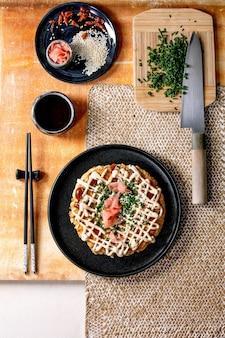 Zelfgemaakte japanse fastfood okonomiyaki kool pannenkoek versierd met lente-ui, ingelegde gember, mayo saus op zwarte keramische plaat met stokjes en ingrediënten hierboven. textuur tafel. plat leggen