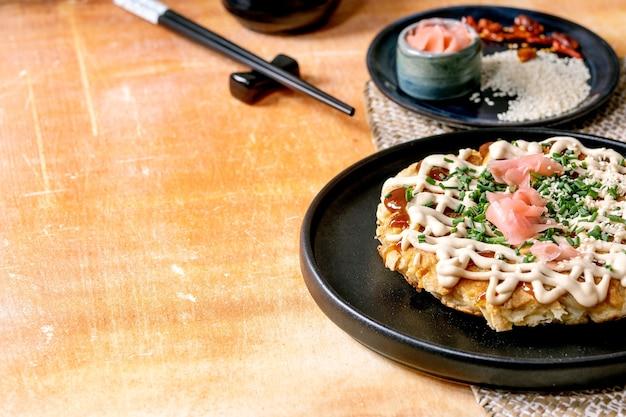 Zelfgemaakte japanse fastfood okonomiyaki kool pannenkoek versierd met lente-ui, ingelegde gember, mayo saus op zwarte keramische plaat met stokjes en ingrediënten hierboven. textuur tafel.