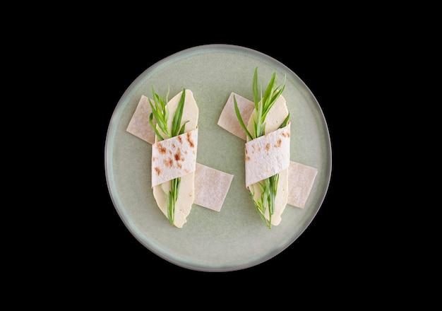 Zelfgemaakte kaas met dragon verpakt in pitabroodje op een groene ronde plaat op een zwarte tafel.