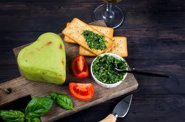 Zelfgemaakte kaaskop met pesto basilicum op oude donkere houten plank en glas wijn op tafel. vers zuivelproduct, gezonde biologische voeding. heerlijk voorgerecht.