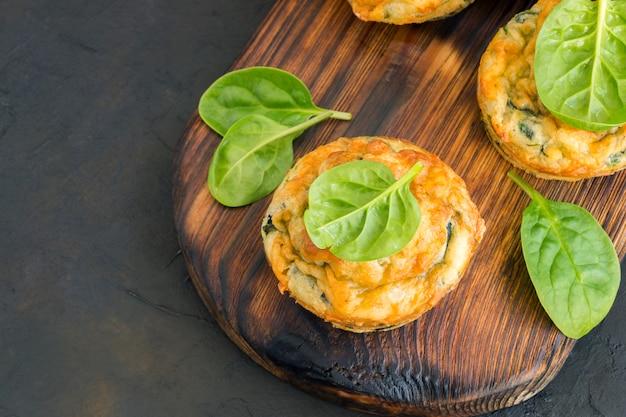 Zelfgemaakte kaasmuffins met spinazie. op een donkere achtergrond.