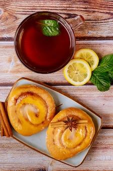 Zelfgemaakte kaneelbroodjes met glazuur en kopje thee met citroen en munt