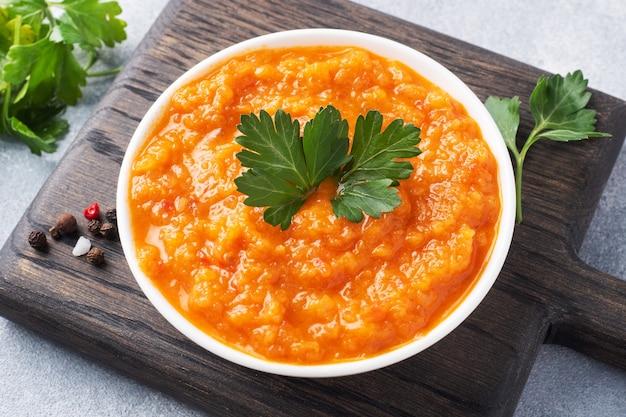 Zelfgemaakte kaviaar van courgette tomaten en uien in een keramische plaat, op een grijze achtergrond. zelfgemaakte productie inblikken, ingeblikte gestoofde groente.
