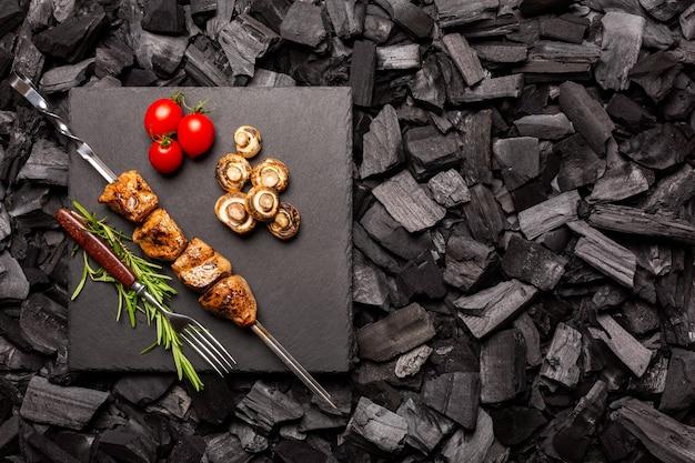 Zelfgemaakte kebab op een snijplank met een achtergrond van houtskool bovenaanzicht