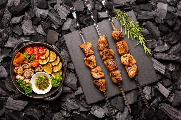 Zelfgemaakte kebab op een stenen snijplank en barbecue groenten in een koekenpan op kolen. bovenaanzicht.