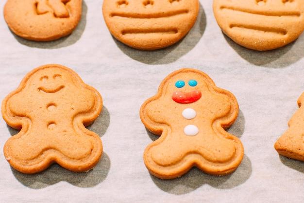 Zelfgemaakte kerst bakkerij bovenaanzicht. feestelijke achtergrond van peperkoekmannen op kookblad
