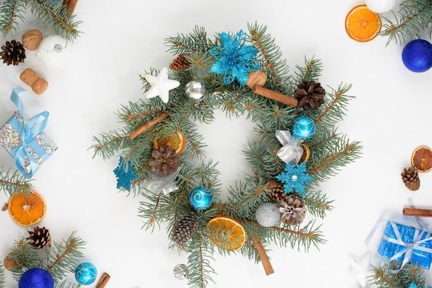 Zelfgemaakte kerstboomkrans van dennentakken op een lichte houten muur met blauwe en zilveren ballen in de kleuren van 2021 stier.
