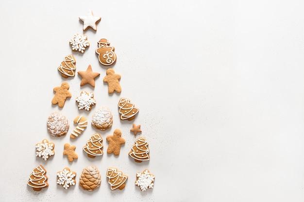 Zelfgemaakte kerstkoekjes gerangschikt als kerstboom op witte achtergrond. xmas wenskaart. uitzicht van boven. plat leggen. ruimte voor tekst.