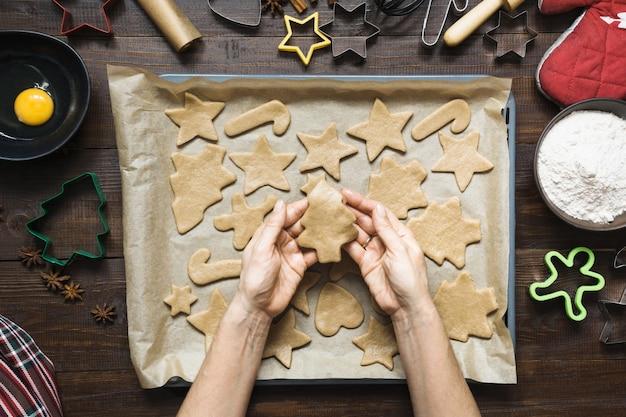 Zelfgemaakte kerstkoekjes op perkament. vrouw rolt deeg. kerstmis. het proces van het bakken van zelfgemaakte koekjes.
