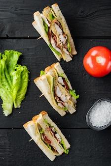 Zelfgemaakte kip sandwich helften, op zwarte houten achtergrond, bovenaanzicht