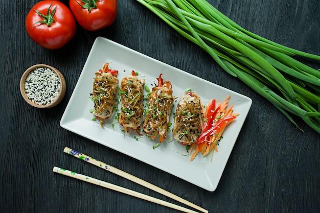 Zelfgemaakte kipfilet rollen met greens, wortel plakjes, paprika op een lichte rechthoekige plaat.