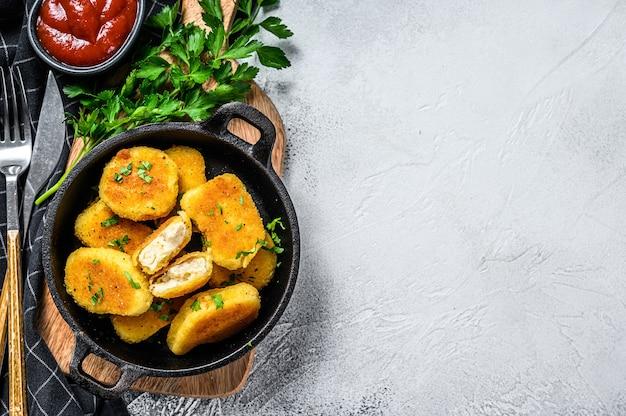Zelfgemaakte kipnuggets en ketchupsaus in een pan. grijze achtergrond. bovenaanzicht. kopieer ruimte.