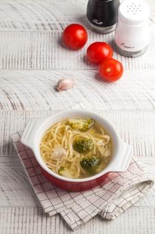 Zelfgemaakte kippensoep met noedels en groenten op een houten tafelblad