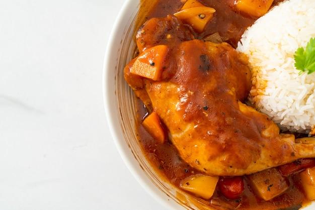 Zelfgemaakte kipstoofpot met tomaten, uien, wortel en aardappelen op bord met rijst