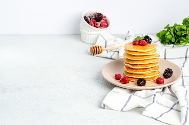 Zelfgemaakte klassieke amerikaanse pannenkoeken met verse frambozen, bramen, honing en muntblaadjes op een rasp, lichte achtergrond.