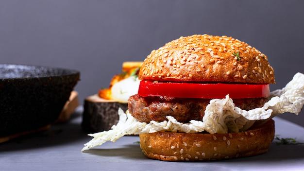 Zelfgemaakte klassieke hamburger met chinese kool, sappige kotelet en paprika op een grijze achtergrond.