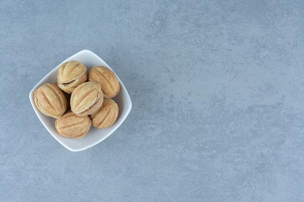 Zelfgemaakte kleine koekjesvorm van walnoten in witte kom over grijs.