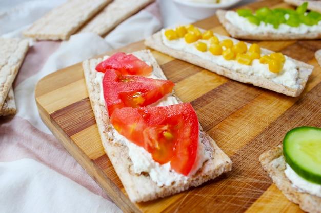 Zelfgemaakte knäckebröd toast met kwark en groene olijven, plakjes kool, tomaten, maïs, groene peper op snijplank. gezond voedselconcept, hoogste mening. plat leggen