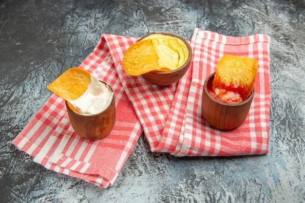 Zelfgemaakte knapperige chips ketchup mayonaise saus op rode gestripte handdoek op grijze tafel