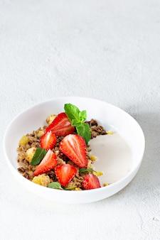 Zelfgemaakte knapperige granola met noten, gedroogde vruchten, verse aardbeien, munt en yoghurt (gefermenteerde gebakken melk) op een witte plaat.