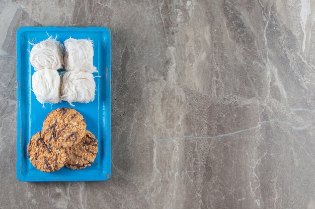 Zelfgemaakte koekjes en turkse suikerspin op een houten bord op blauw.