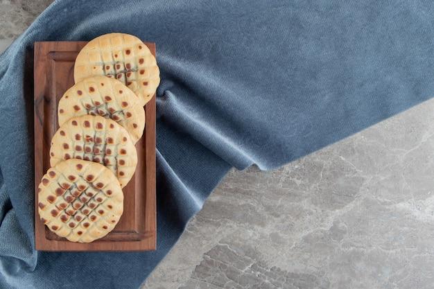 Zelfgemaakte koekjes gevuld met chocolade op een houten bord