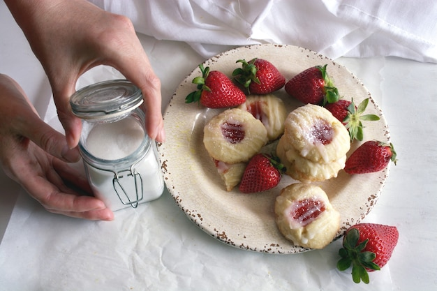 Zelfgemaakte koekjes gevuld met jam en handen open pot met suiker