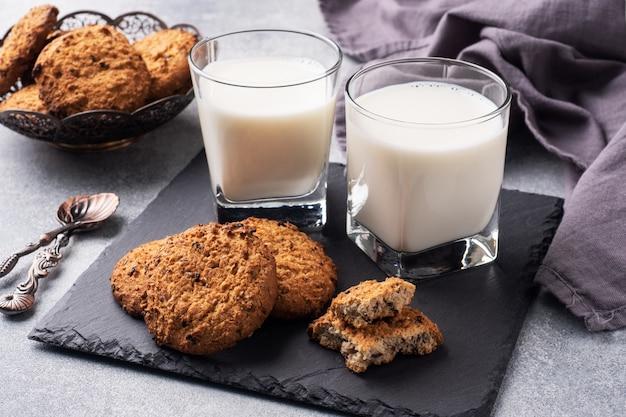 Zelfgemaakte koekjes granen haver en een glas melk op de grijze betonnen tafel.