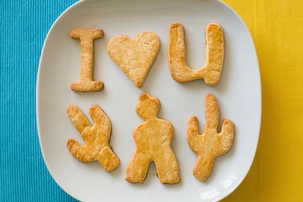 Zelfgemaakte koekjes ik hou van je op een bord en een gele en blauwe achtergrond