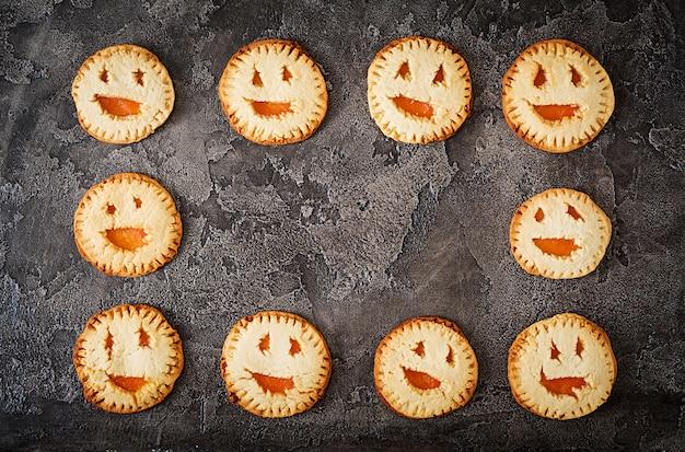 Zelfgemaakte koekjes in de vorm als halloween-hefboom-o-lantaarnpompoenen op de donkere lijst. bovenaanzicht