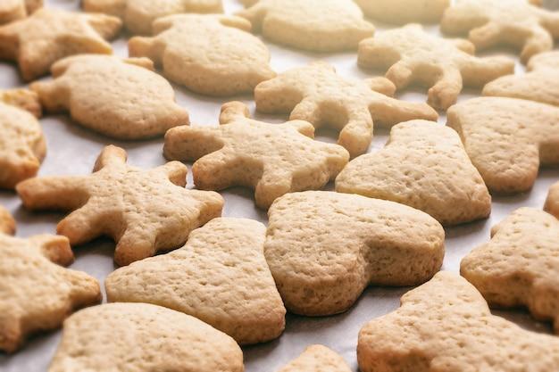 Zelfgemaakte koekjes in de vorm van dieren van verschillende vormen op perkamentpapier, kerst- of nieuwjaarstraktaties, close-up