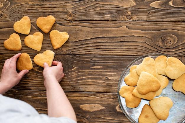 Zelfgemaakte koekjes in de vorm van harten. een persoon beweegt koekjes, zelfgemaakt gebak
