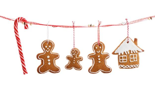 Zelfgemaakte koekjes in de vorm van kerstversiering opknoping op een rood lint geïsoleerd op een witte achtergrond