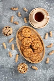 Zelfgemaakte koekjes met biologische pinda's en honing op een houten bord met kopje thee.