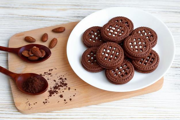 Zelfgemaakte koekjes met cacao, koekjes op een bord, houten lepels met cacao en amandelen