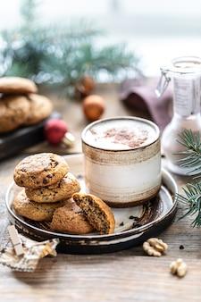 Zelfgemaakte koekjes met noten en koffie in een keramische beker op een houten tafel met speelgoed en kerstboom takken
