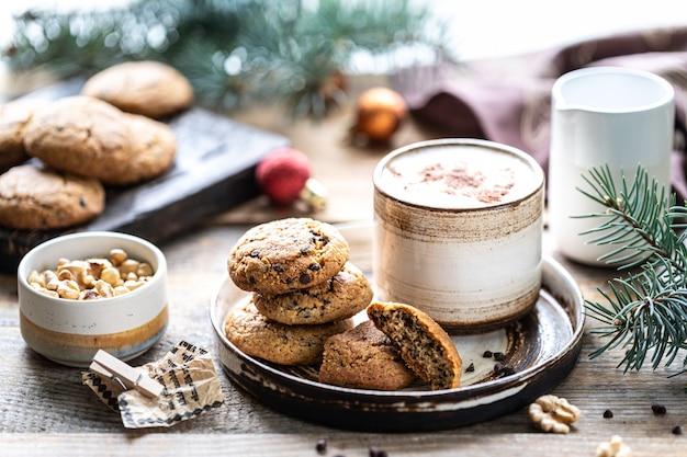Zelfgemaakte koekjes met noten en koffie in een keramische kop op een houten tafel met speelgoed en boomtakken
