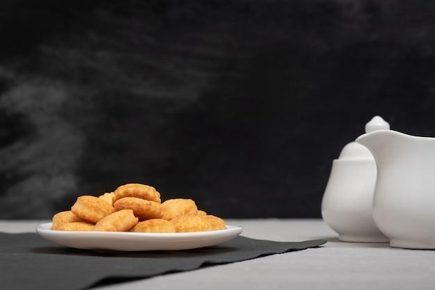 Zelfgemaakte koekjes op de plaat. zwarte achtergrond, creamer en suikerpot. bakken voor thee. heerlijk ontbijt.