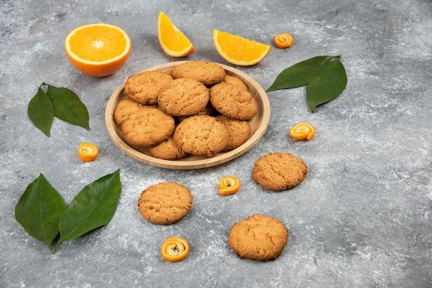 Zelfgemaakte koekjes op een houten bord en stukjes sinaasappel met bladeren over grijs oppervlak.