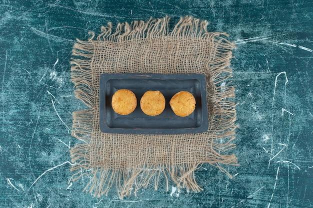 Zelfgemaakte koekjes op een houten plaat op handdoek, op de blauwe achtergrond. hoge kwaliteit foto