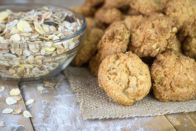 Zelfgemaakte koekjes op een stuk jute en een kom muesli op een houten tafel.