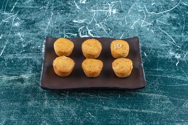 Zelfgemaakte koekjes op een zwarte plaat, op de blauwe tafel.