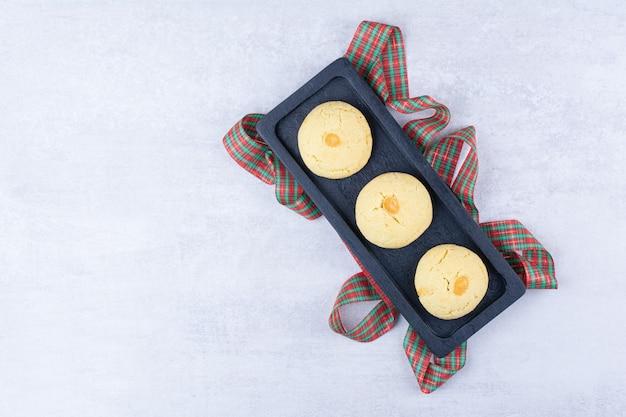 Zelfgemaakte koekjes op zwarte plaat met lint
